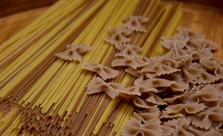 Different types of pasta. Spaghetti and Farfalle Pasta Bows stock images. Dried spaghetti pasta on wooden background. Spaghetti on the table. Wholemeal paste stock images