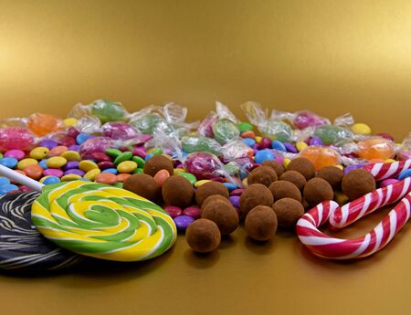 Colorful candies on golden background stock photography. Sweets on golden background. Candies  lollipops images. Luxury candies on golden background with copy space for text Imagens