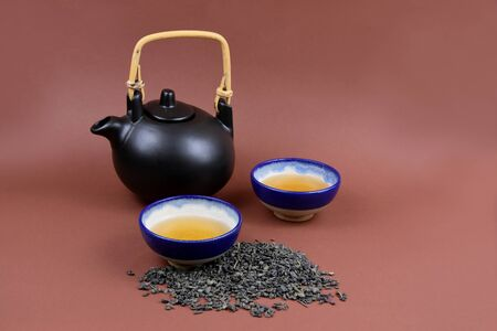 Ceramic teapot stock photography Traditional Chinese tea set frame arrangement. Brown tea set stock images. Cup of loose tea. Loose green tea on brown background with copy space for text Imagens