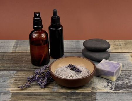 Spa and wellness setting on brown background stock images. Wellness background. Spa still life images. Bath salt in bowl, lava stones and lavender on wooden background