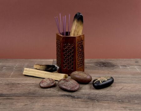 Incense sticks and ritual fumigants stock images. Magical incense stock images. Palo Santo, Sage and Incense. Set of Herbal Fumigants on a Wooden Background. Lines symbols on pebbles