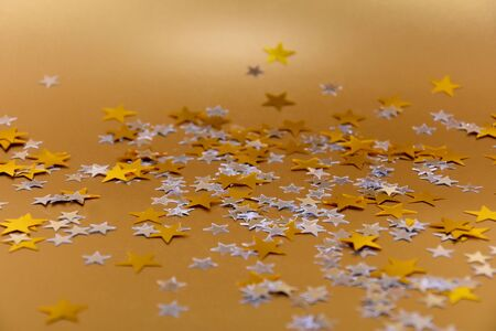 Starry golden background stock images. Elegant golden holiday background. Shiny stars on golden background. Festive background with golden stars