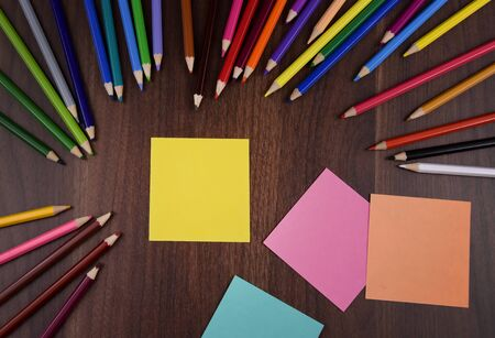 Yellow stick note paper on the table stock images. Crayons on wooden background. Set of colored pencils. School supplies for drawing. Art supplies. Blank note paper. Office supply stock images