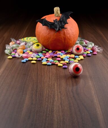 Halloween pumpkin with candy eyes and bat stock images. Halloween pumpkin on wooden background. Scary pumpkin stock photography