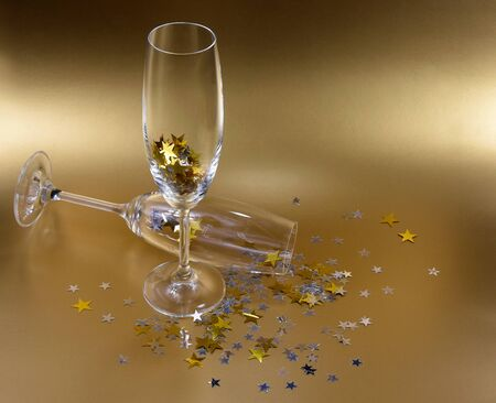 Champagne Glasses With Golden Stars Confetti stock images. Champagne Glasses on a Golden Background. Festive background with golden stars. Elegant golden holiday background Imagens