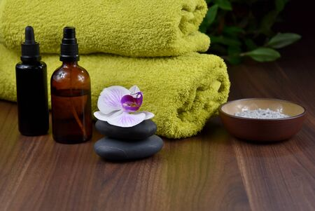 Spa and wellness setting with cosmetic accessories stock images. Massage stones with orchid stock images. Spa concept with zen stones, orchid flower, green towel, cosmetic bottles and salt Stock fotó - 138467541