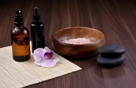 Spa and wellness setting with cosmetic accessories stock images. Massage stones with orchid stock images. Spa concept with zen stones, orchid flower, cosmetic bottles and salt Stock fotó - 138467509