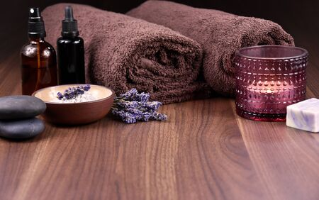 Spa and wellness lavender still life on wooden background stock images. Spa and wellness setting. Bath salt, brown towels, lavender and soap stock images Stok Fotoğraf