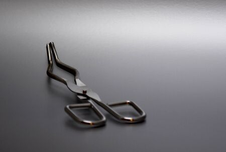 Crucible Tongs stock images. Laboratory tweezers images. Laboratory accessories images. Laboratory equipment on silver background with copy space for text