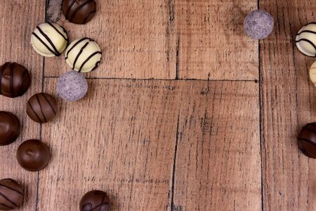 Chocolate pralines frame top view stock images. Chocolate candies on a wooden background. Chocolate frame top view. Chocolate pralines on a wooden table stock images. Border of different candies photo
