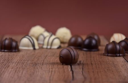 Chocolate pralines on a wooden background stock images. Different types of chocolate candies images. Chocolate candies on a wooden table stock images