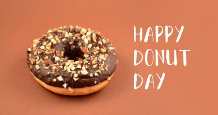 Happy Donut Day inscription with chocolate donut. National Donut Day Poster. Donut with chocolate icing and nuts on a brown background. American delicacy food
