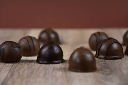 Chocolate pralines on a wooden background stock images. Dark chocolate candies images. Chocolate candies on the table stock images