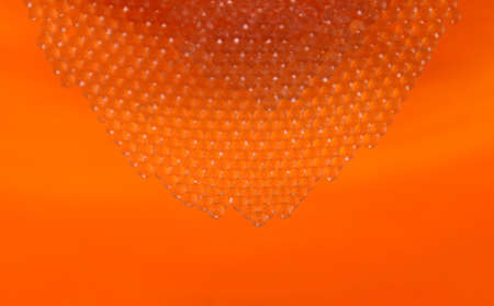 Small glass solid balls orange background stock images. Pile of crystal clear beads images. Shiny orange background texture images. Small solid borosilicate glass balls images 写真素材