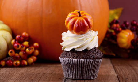 Halloween cupcake with pumpkin stock images. Pumpkin cupcake with cream stock images. Autumn still life with pumpkin cupcake. Sweet halloween decoration stock photo. Beautiful autumn background images