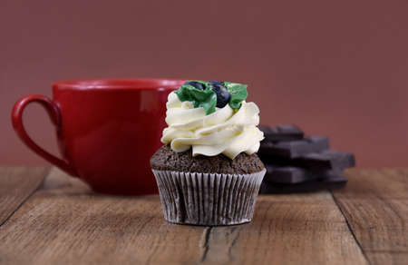 Chocolate cupcake with vanilla frosting still life stock images. Cream cupcake isolated on a brown background with copy space for text. Delicious cupcake on a wooden background. Cake on the table 스톡 콘텐츠