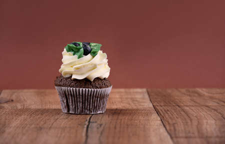 Chocolate cupcake with vanilla frosting on a wooden background stock images. Cupcake on the table. Delicious cupcake brown frame stock images. Chocolate cupcake brown border with copy space for text 스톡 콘텐츠
