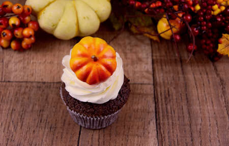 Halloween cupcake with pumpkin on a wooden background stock images. Pumpkin cupcake with vanilla cream stock images. Autumn still life with pumpkin cupcake. Sweet halloween decoration stock photo