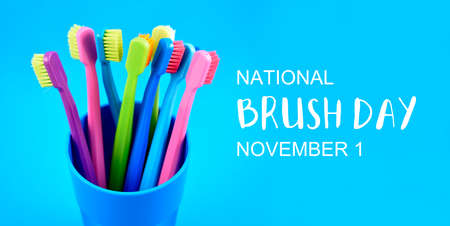 National Brush Day stock images. Colored toothbrushes stock images. Morning hygiene concept. Bathroom accessories images. Toothbrushes in a cup photo. Brush Day Poster, November 1. Important day