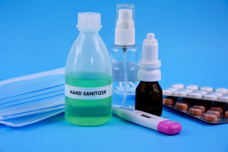 Hand sanitizer gel, medication, thermometer and protective face mask stock images. Protective equipment against COVID-19. Sanitizer gel bottle with medical mask and drugs isolated on a blue background Фото со стока