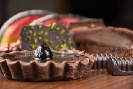 Pile of heap of various cakes stock images. Chocolate tart with cherries images. Different types of desserts stock photo. Creamy chocolate cakes images Фото со стока