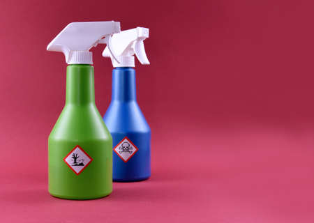 Plastic spray bottle with toxic liquid and hazard symbol stock images. Household chemistry photo. Container with poisonous liquid. Plastic spray bottle isolated on a red background with copy space