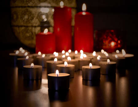 Many burning tealight candles stock images. Christmas still life with candles stock photo. Romantic still life with red candles stock images. Beautiful christmas candles stock images Imagens