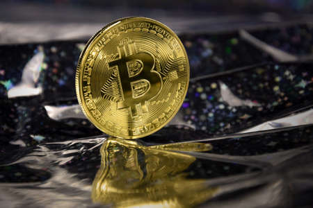 One bitcoin golden coin stock images. Cryptocurrency on a shiny dark background. Digital gold images. Beautiful gold bitcoin coin photo images