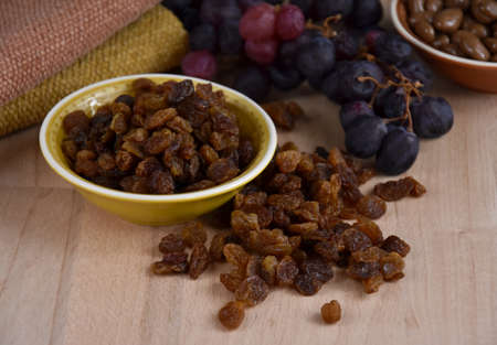 Dried raisins with a bunch of grapes stock images. Raisins sultanas still life photo images. Drying grapes and raisins in chocolate images