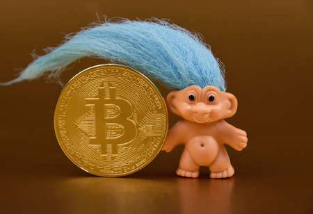 One bitcoin golden coin with blue hairy figure stock images. Haired doll with bitcoin on a golden background photo images