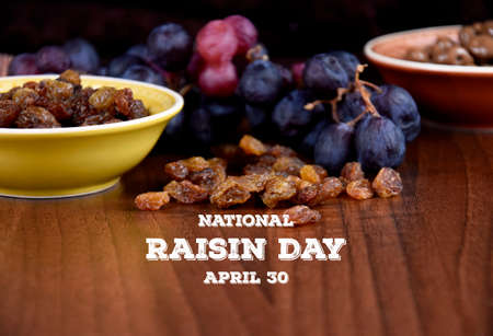 National Raisin Day stock images. Dried raisins with a bunch of grapes on a wooden background stock images. Raisins sultanas still life photo images. Drying grapes on the table images. Important day Foto de archivo