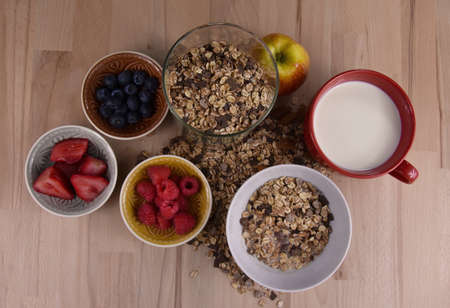 Healthy breakfast with muesli and fruits on the table top view stock images. Bowl of muesli with milk and fruits on a wooden background stock photo