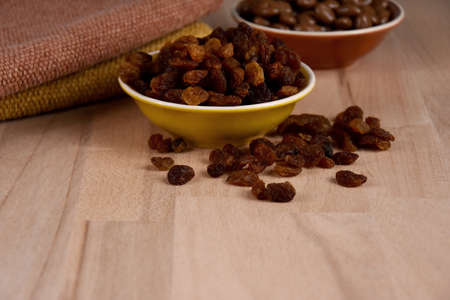 Dried raisins in a bowl on a wooden background stock images. Raisins sultanas still life photo images. Raisins on the table stock images. Raisins on a wooden background with copy space for text Foto de archivo