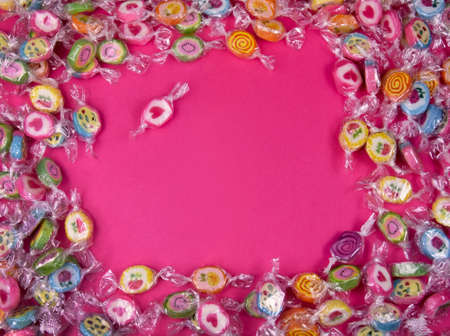 Colorful candies on a pink background top view stock images. Sweets on a pink background with copy space for text. Pile of candies on a pink background frame. Candy with heart stock images Foto de archivo