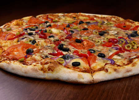 Whole delicious vegetarian pizza stock images. Veggie pizza with tomatoes, cheese, olives, mushrooms and peppers on the table stock photo. Vegetable pizza without meat close-up images