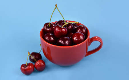 Sweet ripe cherries in a red mug stock images. Fresh cherries on a blue background stock images. Sweet cherry fruit berries detail photo images Imagens