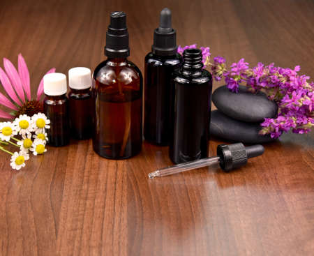 Spa and wellness setting with flowers and glass cosmetic bottles stock images. Bottles with essential oils and flowers still life stock photo. brown glass vial with dropper with flowers and herbs Imagens