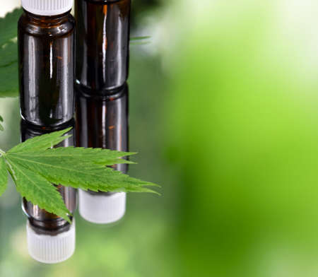 Bottle of CBD oil with hemp leaf stock images. Cannabis oil bottle isolated on a green background with copy space for text. Hemp cosmetics green background frame Imagens