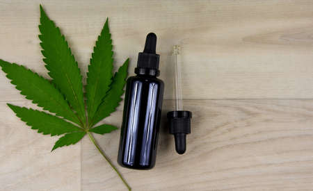Glass bottle of CBD oil with hemp leaf top view stock images. Cannabis oil bottle with a dropper on a wooden background. Hemp cosmetics stock images. Brown glass vial with cannabis extract stock photo Imagens