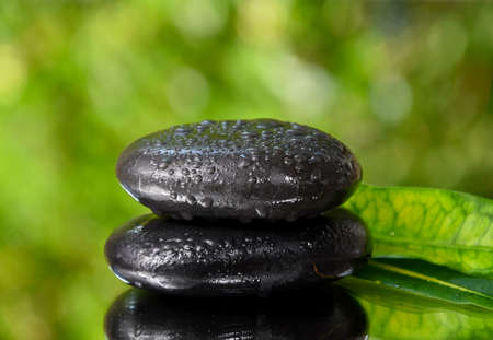 Spa massage stones on a fresh green background stock images. Spa and wellness frame stock images. Pile of black stones photo. Spa-concept with zen stones with copy space for text