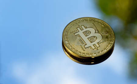 One bitcoin golden coin stock images. Cryptocurrency isolated on a natural blue sky background. Digital gold images. Bright gold bitcoin coin frame photo images