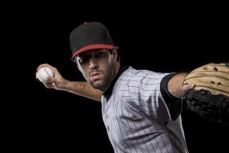 Baseball Player pitching a ball on a black background. Studio Shot. Standard-Bild