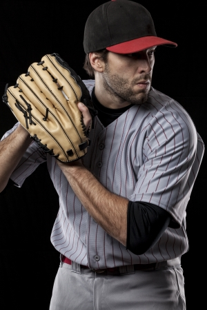 Baseball Player pitching a ball on a black background. Studio Shot. photo