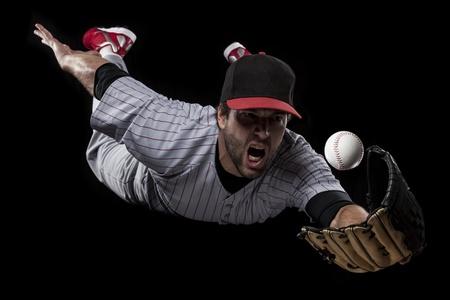 pelota beisbol: Jugador de b?isbol que coge una bola sobre un fondo negro. Tiro del estudio.
