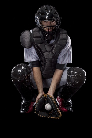 Baseball Player, catcher catching a wild pitch, on a black background. Studio Shot. photo