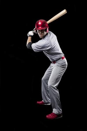 pelota de beisbol: Jugador de b?isbol sobre un fondo negro. Tiro del estudio. Foto de archivo