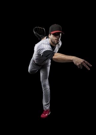 baseball bat: Baseball Player pitching a ball on a black background. Studio Shot. Stock Photo