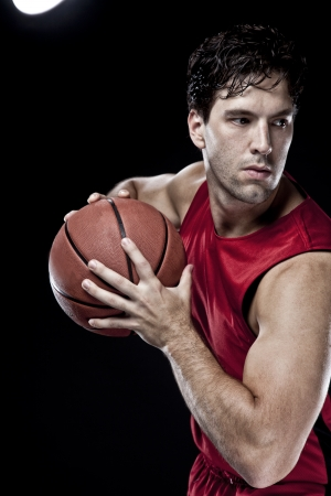 a basketball player: Basketball player with a ball in his hands and a red uniform. photography studio. Stock Photo