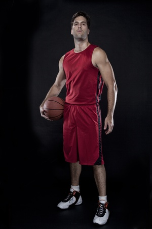 basketball player: Basketball player with a ball in his hands and a red uniform. photography studio. Stock Photo