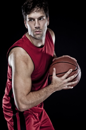 basketball team: Basketball player with a ball in his hands and a red uniform. photography studio. Stock Photo